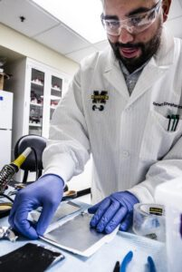 Ahmet Emrehan Emre, a biomedical engineering PhD candidate, sandwiches a thin sheet of a cartilage-like material between a layer of zinc on top and a layer of manganese oxide underneath to form a battery. Image credit: Evan Dougherty/Michigan Engineering